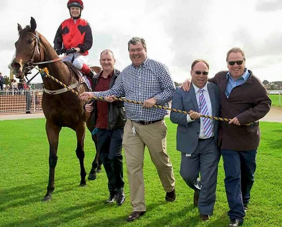 MADASSABelmont winner returns to scale with his jubilant ownersPhoto / Western Racepix
